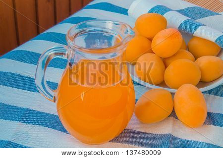 Fresh apricot juice in a glass jar, apricots on striped napkin.