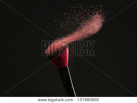 Makeup brush with flying powder on black background