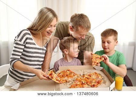 Happy lovely family eating pizza