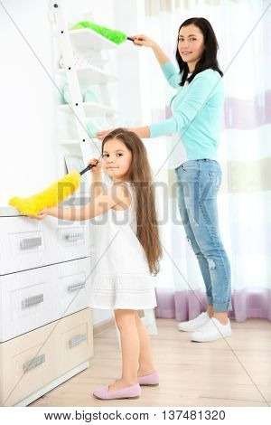 Daughter and mother cleaning dust in room