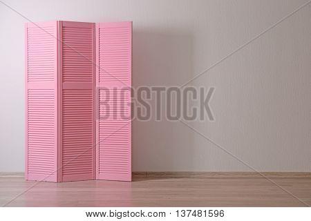 Pink folding screen in room