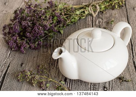 Teapot and herb oregano on a wooden table.