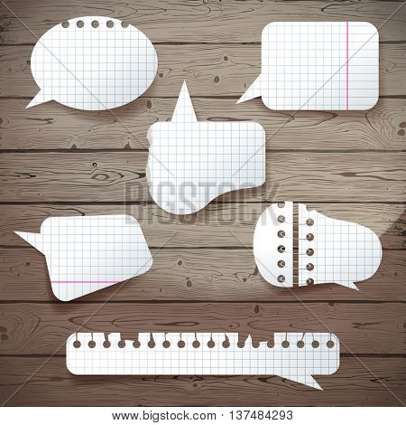 Paper speech bubbles over wooden background