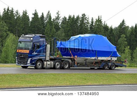 PAIMIO, FINLAND - JUNE 23, 2016: Blue Volvo FH semi truck hauls a boat as exceptional load along freeway. Abnormal transport permit is required if any dimension of the load exceeds the free dimension limits.