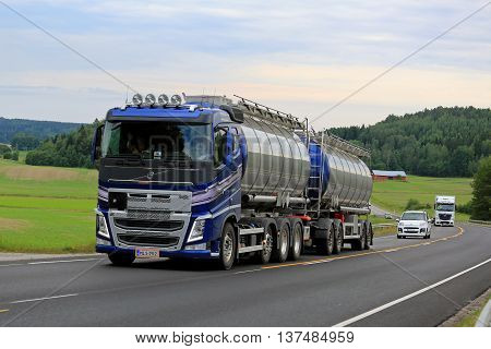 SALO, FINLAND - JUNE 26, 2016: New blue Volvo FH tank truck moves uphill along scenic road among traffic on an overcast summer afternoon in South of Finland.