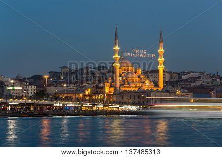 ISTANBUL TURKEY - JUNE 20 2015: Night view on Galata bridge and New Mosque in Eminonu Istanbul Turkey