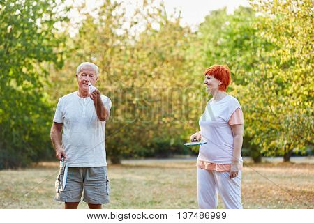 Senior couple playing badminton in the park in the garden