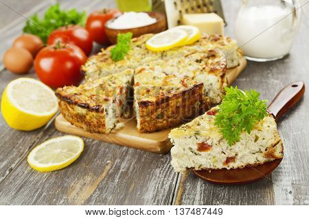 Fish pie with tomatoes and herbs on the table