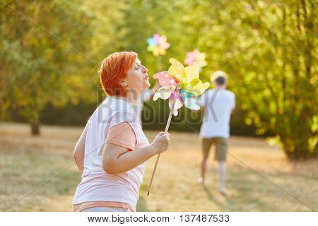 Senior woman playing with a pinwheel in the summer in the park