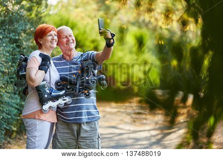 Happy senior couple taking a selfie with their inline saktes in the nature