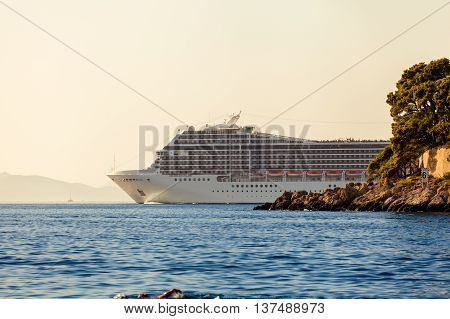 Beautiful white cruise liner goes into the sea after a tour of Dubrovnik. Cruise on the Adriatic Sea. Croatia.