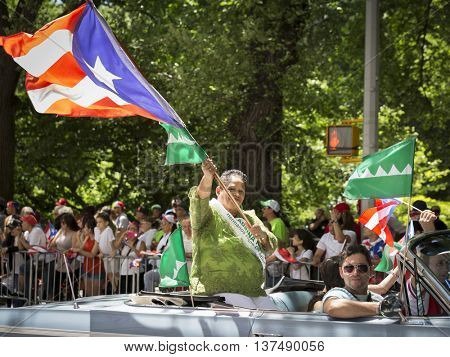 NEW YORK - JUNE 12 2016: An honoree rides in a classic car waving the Puerto Rican flag during the 59th annual National Puerto Rican Day Parade on 5th Avenue in New York City on June 12 2016.