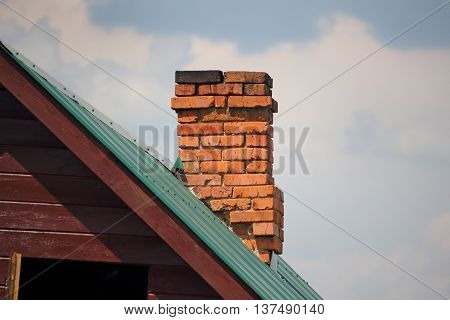 Brick chimney on the green metal roof photo