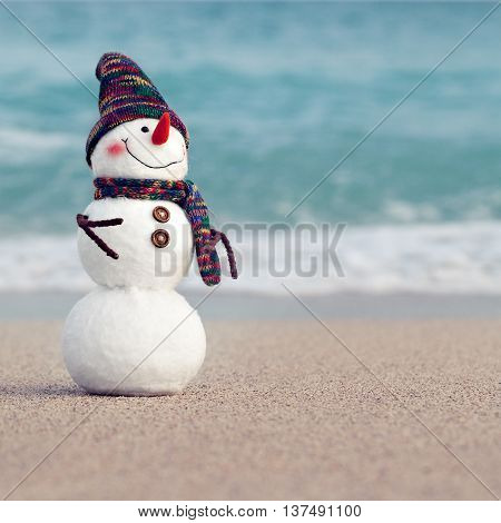 Smiling snowman on the sea beach. Summer holidays or New Year concept