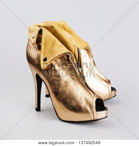 Stylish golden female shoes in a grey background