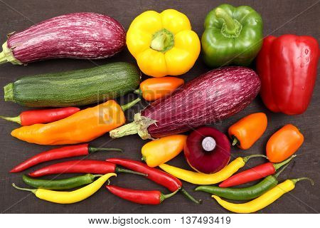 Assorted colorful varieties of hot and sweet peppers and eggplant sitting on table.