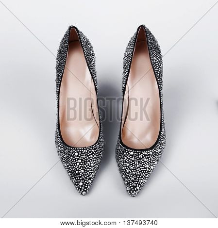 women's shoes inlaid with crystals in grey background