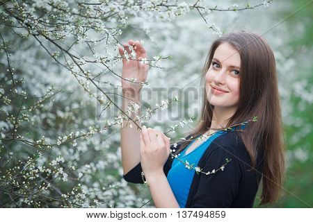 Portrait of a brunette woman inhales the scent of flowers