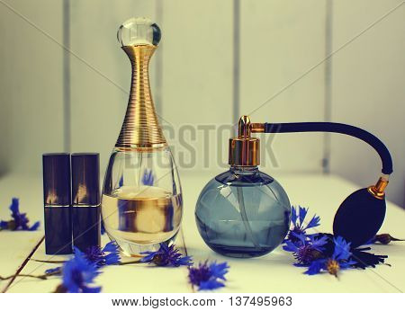 women's cosmetics. Two bottles of perfume and lipstick