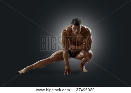 Muscular man squatted down his leg to the side