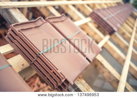 Brown Roof Tile Packs At House Construction Site. Roof Under Construction With Modern Tiles