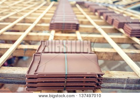 Roof Under Construction With Stacks Of Brown Roof Tiles Prepared On Wooden Structure