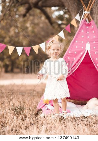 Happy kid girl 2-3 year old playing over wigwam outdoors