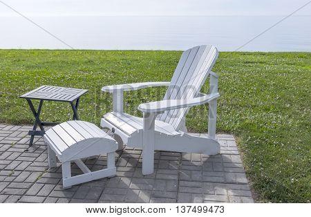 Serene Scene of a White Adirondack Chair by Lake Erie