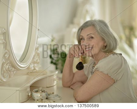 Senior woman portrait with make up brush