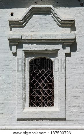 Small window of ancient building of white color with a metal lattice