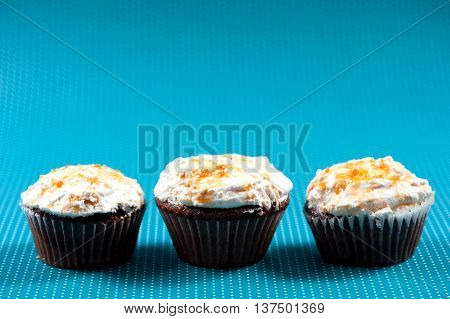 Three Muffins With Vanilla And Sweet Sugar Topping Against Blue