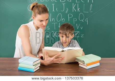 Pupil Reading With Female Teacher In Front Of Green Chalkboard