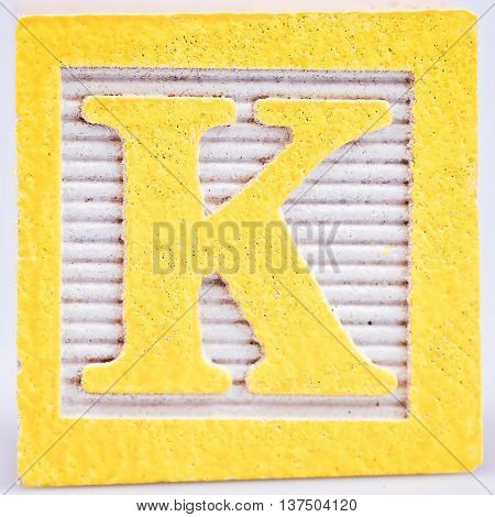 Yellow letter K painted wood block distressed