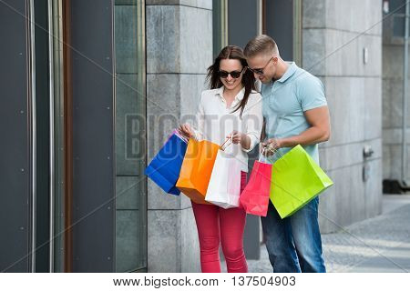 Young Happy Couple Standing On Footpath Holding Multi-colored Shopping Bags