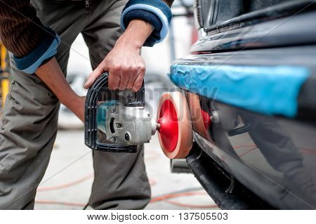 Professional Mechanic Using A Power Buffer Machine For Cleaning