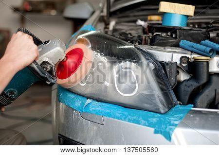 Auto Mechanic Enginner Polishing A Headlight Of A Modern Car Wit