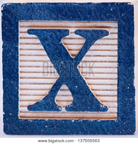 Blue letter X painted wood block distressed