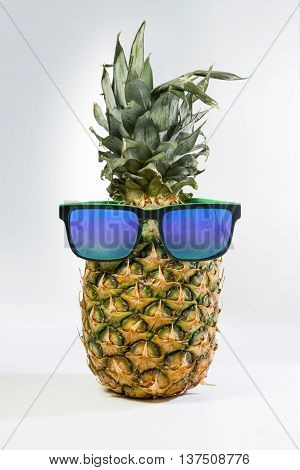 Summer concept pineapple fruit with colorful hipster sunglasses on studio background. Includes clipping path.