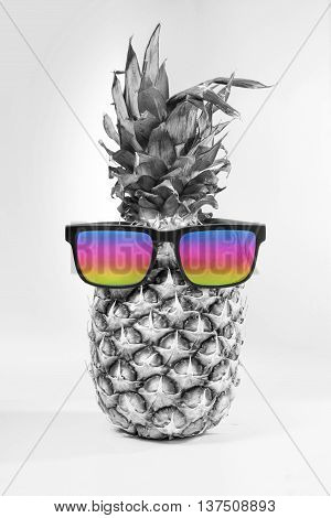 Happy summer concept idea black and white pineapple fruit wearing colorful hipster sunglasses on isolated background. Includes clipping path.