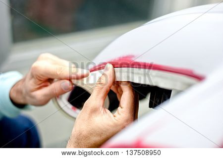 Mechanic Preparing A Car For Painting By Protecting The Edges