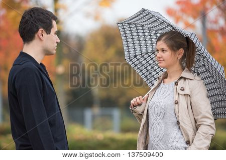 Young couple in autumn park woman standing under umbrella wearing beige mackintosh