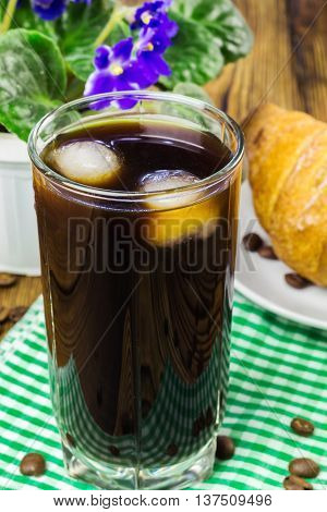 Glassful of black coffee with ice on green napkin. croissant flowerpot wooden table selective focus.