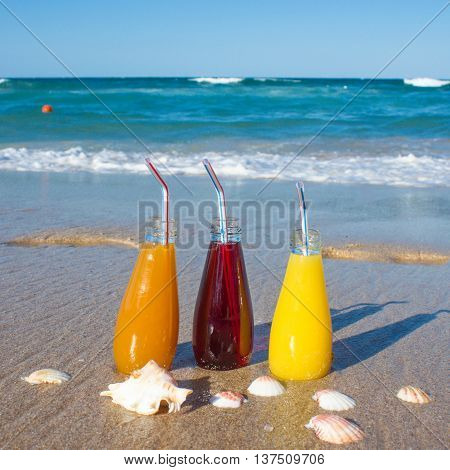 Juice Bottles With Blue Straws Sand Beach Blue Sea Background Summer Holiday Concept