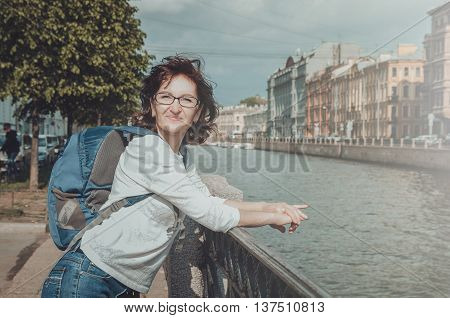 Summer portrait of happy middle woman tourist with glasses dressed in casual white blouse blue backpack on her shoulder. Smiling female standing on the embankment Moyka river channel near and famous Saint Isaac cathedral or Isaakievskiy Sobor in Saint-Pet