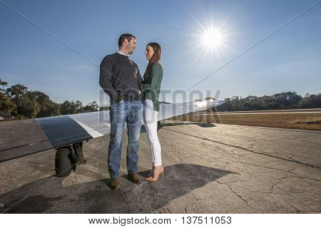 Rich boyfriend and girlfriend with private plane on tarmac