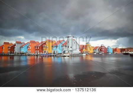 colorful buildings on water during storm Groningen Netherlands