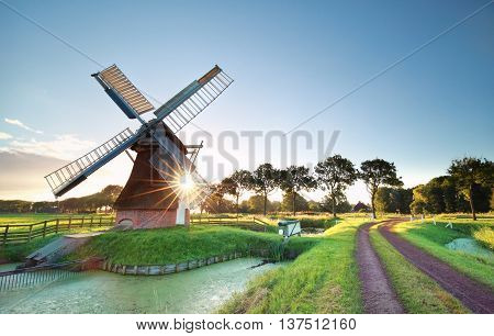 morning sunshine behind Dutch windmill in Holland