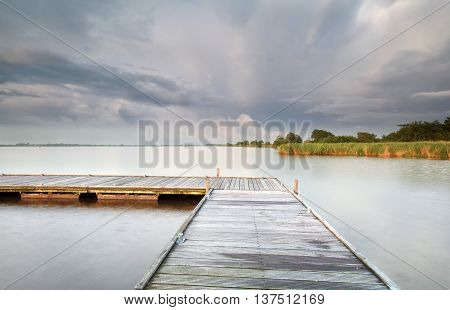 wooden pier on big lake and clouded sky Holland