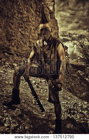 Cruel horrible post-apocalyptic raider with hand-made sword posing on a wasteland