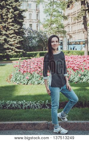 Summer lifestyle portrait of young stylish brunette woman with long hair wearing in casual jeans denim clothes. Smiling female walking in bloom park near famous Nevsky prospect in Saint-Petersburg Russia. Travel concept in European city.